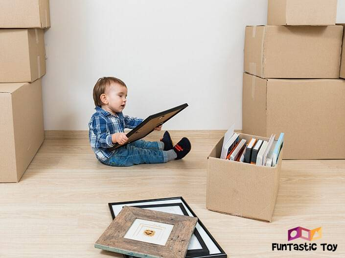 Little Boy Playing With Cardboard Boxes and Picture Frames