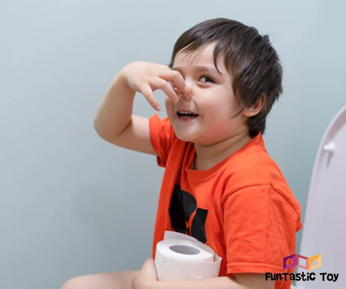 Image of boy in orange shirt on toilet seat