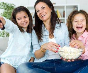 Featured image of smiling mother with two girls watching TV