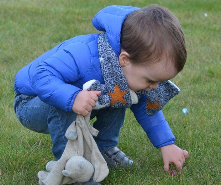 Image of child picking up easter egg
