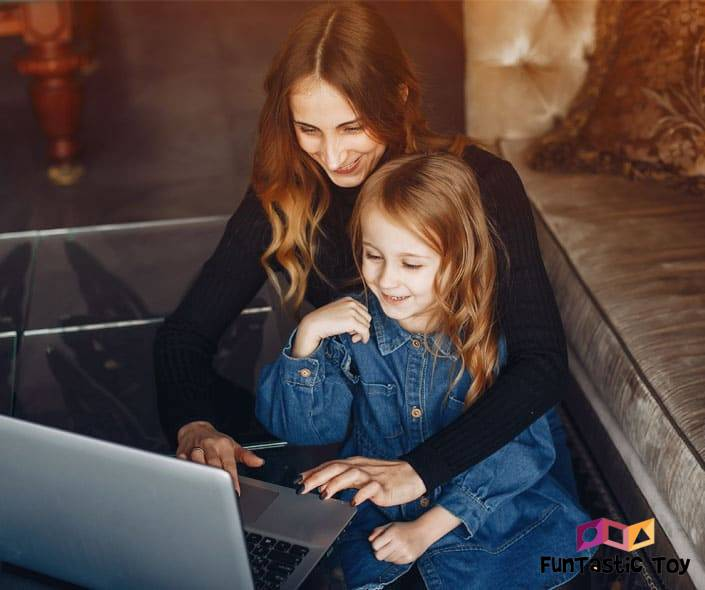 Image of smiling mother and daughter with laptop