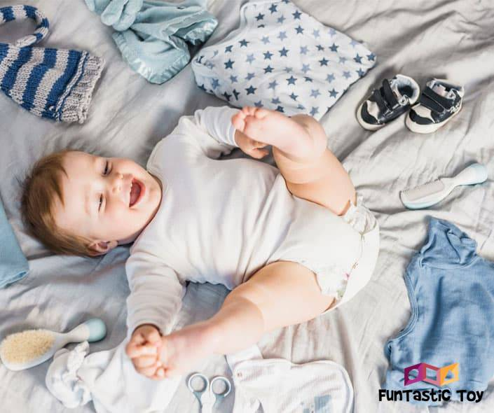 Featured image of smiling baby boy on bed with clothes