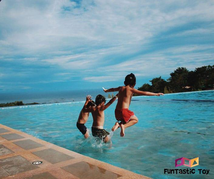 Image of three boys jumping in pool