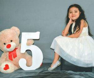 Featured image of five-year-old girl sitting next to big teddy bear
