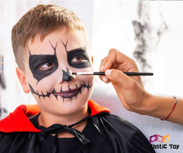 Image of boy in costume getting face painted