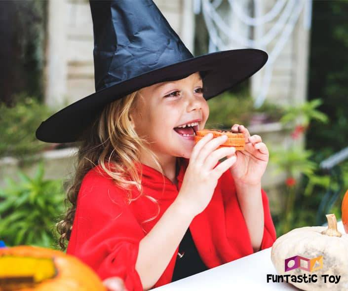 Image of little girl in witch costume eating cookie