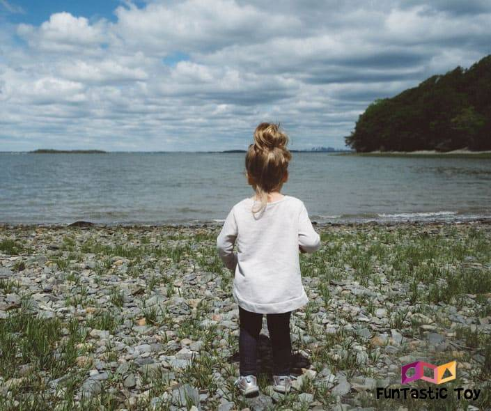 Image of little girl with bun on shore