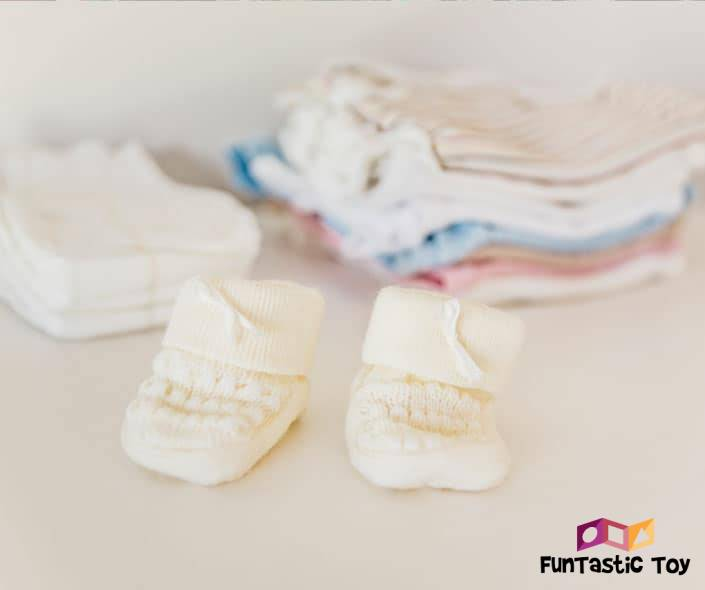 Image of stacked baby clothes with tiny slippers