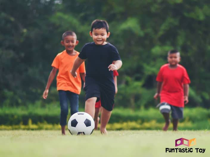 Image of three boys playing soccer
