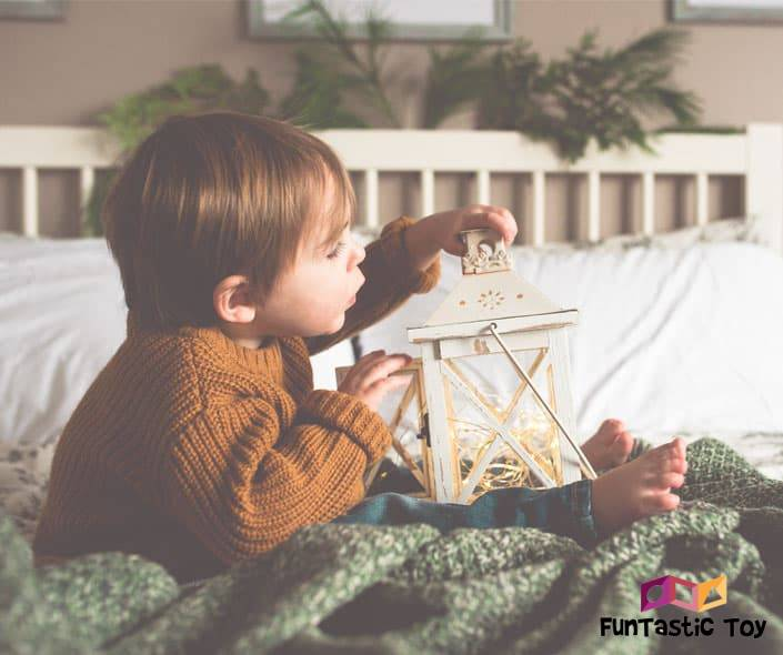 Image of toddler boy with lamp sitting on bed