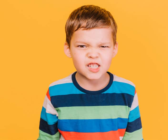 Image of angry boy on orange background
