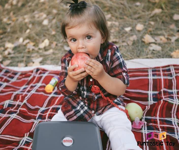 Image of baby girl eating fruit on picnic