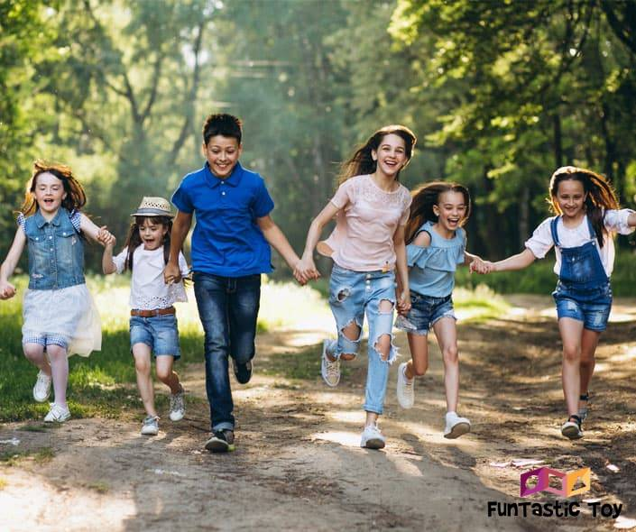 Image of group of kids holding hands running in park