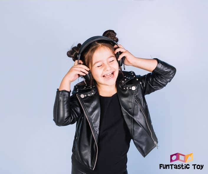 Image of happy little girl with headphones and leather jacket