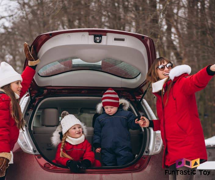 Image of mother with three children in car in winter