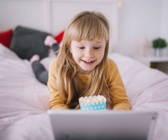 Featured image of little girl on bed with popcorn watching cartoons