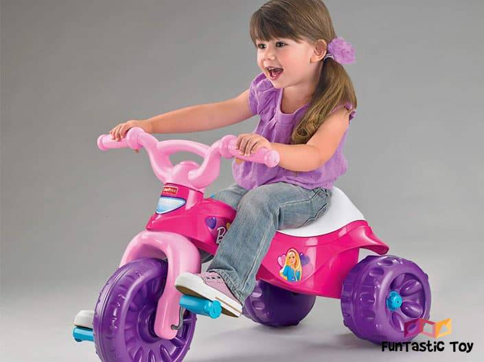Image of cute girl riding Fisher-Price Barbie Tough Trike Princess Ride-On