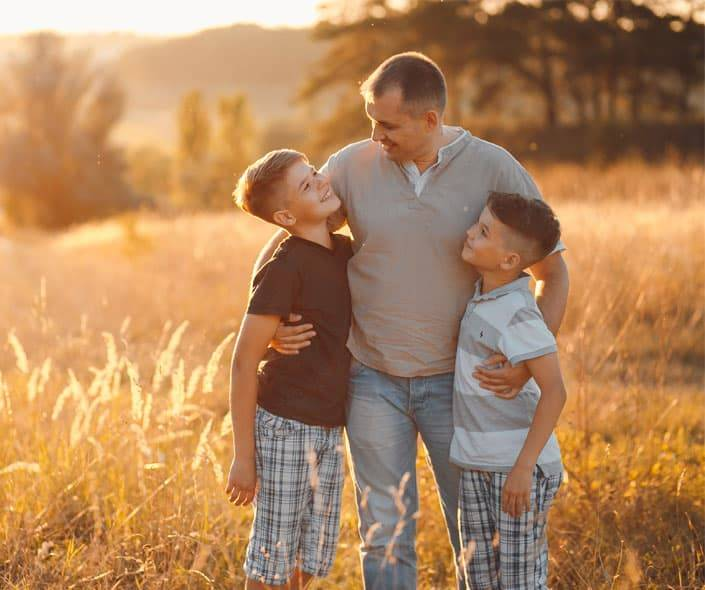 Image of father hugging two sons in field at sunset