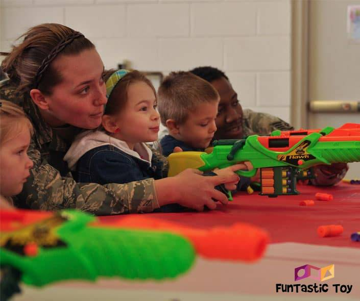 Image of soldiers teaching children to shoot nerf guns